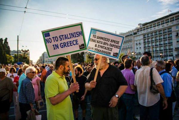"""Deux manifestants. La pancarte de gauche dit: 80% de la dette c'est les retraites et salaires des fonctionnaires"""". Celle de gauche """"Non au stalinisme en Grèce"""""""